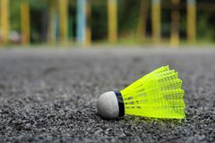 Shuttlecock with a white tip and a light green shank on the gaming, fenced net, site.  royalty free stock image