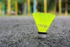 Shuttlecock with a white tip and a light green shank on the gaming, fenced net, site.  royalty free stock photography