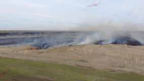Volando avanti diritto sopra il campo bruciante Fuoco e fumo, terra carbonizzata nera emergenza archivi video