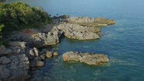 Volando in basso sopra la linea adriatica della costa con i cespugli verdi delle pietre e la chiara acqua di mare stock footage
