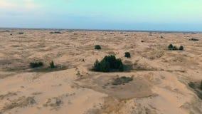 Volando indietro sopra le dune di sabbia pittoresche in deserto stock footage