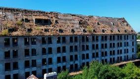 Volando lentamente hacia el edificio industrial arruinado y destruido viejo, visión aérea almacen de metraje de vídeo