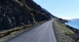 Volando lungo un fiordo in Islanda con le cascate della molla stock footage