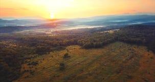 Volando sobre el bosque verde, colinas cubiertas con la niebla, sol rojo que va abajo Rusia almacen de video