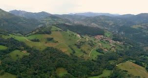 Volando sobre las colinas con la vista del bosque, de un pueblo y de la formación de la montaña almacen de video