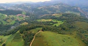Volando sobre las colinas con la vista del bosque, de un pueblo y de montañas en el horizonte metrajes