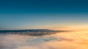 Volando sobre las nubes, mañana hermosa sobre la ciudad Imágenes de archivo libres de regalías
