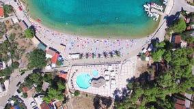 Volando sobre los apartamentos turísticos en la bahía arenosa blanca de la isla de Solta, Croacia almacen de metraje de vídeo