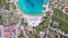 Volando sobre los apartamentos turísticos en la bahía arenosa blanca de la isla de Solta, Croacia almacen de video