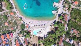 Volando sobre los apartamentos turísticos en la bahía arenosa blanca de la isla de Solta, Croacia metrajes