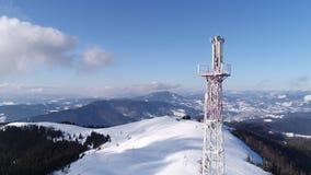 Volando sobre torre de comunicaciones, paisaje nevado del invierno de la montaña almacen de metraje de vídeo