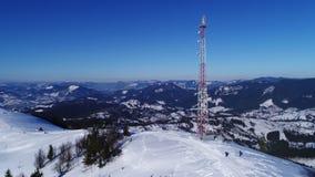 Volando sobre torre de comunicaciones, paisaje nevado del invierno de la montaña metrajes