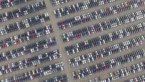 Volando sopra il parcheggio di stoccaggio di nuove automobili invendute, vista aerea stock footage