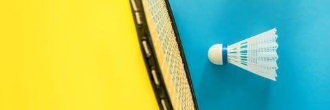 Volant en racket voor het spelen van badminton op gele achtergrond Het concept de zomervermaak Minimalismpop-art stock afbeelding