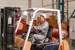 Volant et leviers en gros plan Équipez conduire un chariot élévateur par un entrepôt dans une usine conducteur dans l'uniforme et photos libres de droits