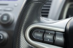 Volante ascendente próximo com close-up dos botões do controle Controle de sistema estereofônico do carro imagens de stock