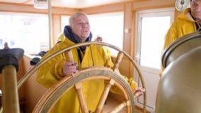 Volante di giro della donna anziana sul ponte di capitano alla nave di navigazione Timone maturo della direzione della donna di c stock footage