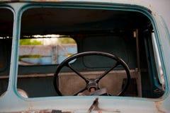Volante negro retro dentro del camión azul viejo y abandonado Imagenes de archivo