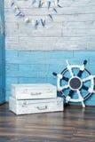 Volante y maletas blancas que se colocan en la pared azul de madera Fotos de archivo libres de regalías