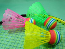 Volants en plastique de Colourfull sur la raquette de badminton photographie stock