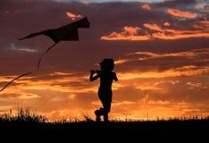 Volar una cometa en la puesta del sol. Fotografía de archivo