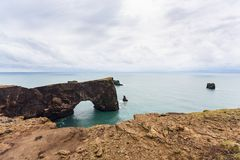 Volcanic arch on Dyrholaey promontory in Iceland. Travel to Iceland - volcanic arch on Dyrholaey promontory, near Vik I Myrdal village on Atlantic South Coast in royalty free stock photos