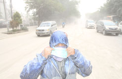 Volcanic ash from mount kelud eruption. INDONESIA, SOLO : SOLO, INDONESIA – FEBRUARY 14: activists handed out masks to road users. Solo city of stock image