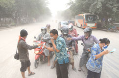 Volcanic ash from mount kelud eruption. INDONESIA, SOLO : SOLO, INDONESIA – FEBRUARY 14: activists handed out masks to road users. Solo city of stock photos