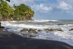 Volcanic black lava sand at the small Saint-Sauveur beach on Guadeloupe stock image