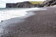 Volcanic black sand and volcanic rocks on the Iceland beach Royalty Free Stock Photo