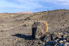 Volcanic bomb in front of volcano Montana Colorada in Lanzarote, Royalty Free Stock Photography