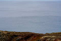Volcanic cliff in front of the ocean. View from a volcanic cliff to the ocean Royalty Free Stock Photo