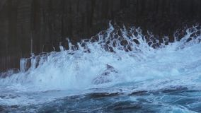 Volcanic coastline cliff and waves breaking in super slow motion stock video footage