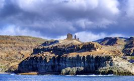 Volcanic coastline in Puerto Rico , Gran Canaria from the ocean. Under a cloudy sky royalty free stock photography