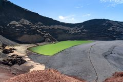 Volcanic crater and green lake at El Golfo, Lanzarote, Canary is Royalty Free Stock Photography