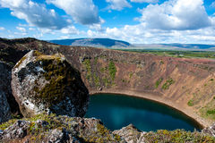 Volcanic crater Kerid with blue lake inside, at sunny day with beautiful sky, Iceland. Volcanic crater Kerid with blue lake inside and huge stone, at sunny day Royalty Free Stock Image