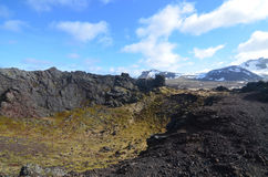 Volcanic Crater with Lava Rock and Scenic Mountains Stock Photo
