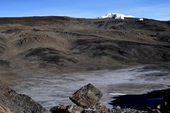 Volcanic crater on summit of Mount Kilimanjaro with melting glacier in background. Blue sky looking into crater from Rongai route Royalty Free Stock Images