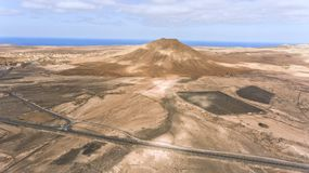 Volcanic desert panorama with Atlantic Ocean crossing highways . Aerial view of roads crossing desert landscape, panorama of volcanic mountains, coastline of Royalty Free Stock Photo
