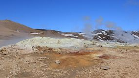 Geyser on open space and lava stone stock images