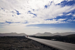 Volcanic landscape and cloudscape - road on Lanzarote Royalty Free Stock Photo