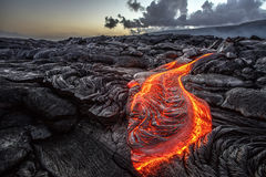 Volcanic landscape with hot lava on the ground. Red Orange vibrant Molten Lava flowing onto grey lavafield and glossy rocky land near hawaiian volcano with vog Royalty Free Stock Image