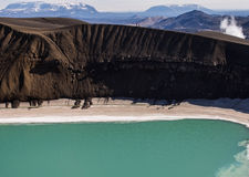 Volcanic landscape in Iceland. Volcanic landscape with snow, a crater, blue water and mountains in June, during the midnight sun in Iceland Stock Photography