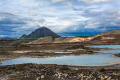 Volcanic landscape of Iceland. Turquoise hot pools and a mighty volcano at Namafjall, Myvatn area - Iceland Royalty Free Stock Images