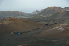 Volcanic landscape, Lanzarote, Spain, craters, blue touristic bus Royalty Free Stock Photography