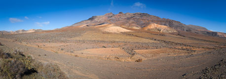 Volcanic landscape with mountain in the background. Dry volcanic landscape with mountain in the background and a clear blue sky Stock Image