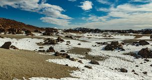 Volcanic landscape of Tenerife with dry lava rocks covered by snow in foreground. Canary Islands, Spain. Teide National Park royalty free stock photography