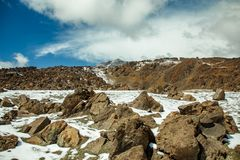 Volcanic landscape of Tenerife with dry lava rocks covered by snow in foreground. Canary Islands, Spain. Teide National Park royalty free stock image