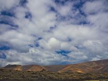 Volcanic lava and mountains against the blue sky with white clouds. Orzola, Lanzarote Stock Photos