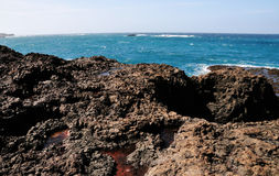 Volcanic lava rock waterfront Stock Images